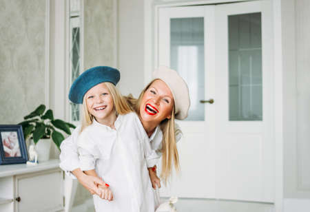 Young funny happy fair long hair mom and her cute girl having fun together at living room, happy family lifestyle