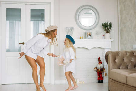 Young funny happy fair long hair mom and her cute girl having fun together dancing at the living room, happy family lifestyle