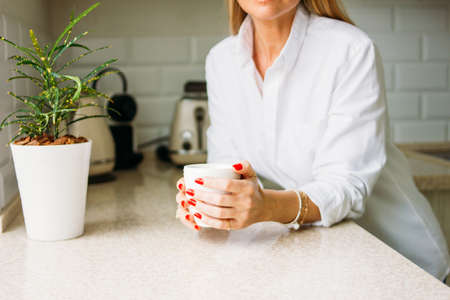 Crop photo of charming blonde woman with long fair hair in white shirt with morning cup of the tea in hands on bright kitchen before working day.