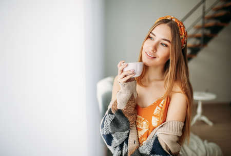 Beautiful smiling young woman fair long hair girl wearing in the cozy knitted cardigan with cup of tea near window at home