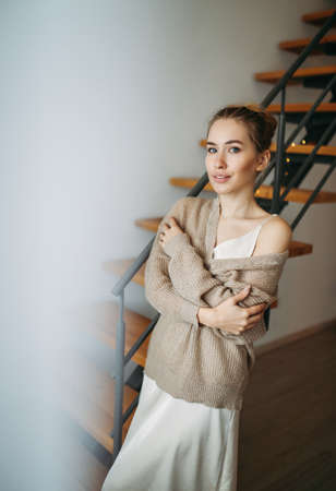 Young beautiful girl with blonde hair in evening beige silk dress and cozy cardigan in front of the stairs at home