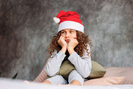 Curly haired beautiful tween girl in Santa hat and pajamas sitting on bed with pillow, christmas morning time