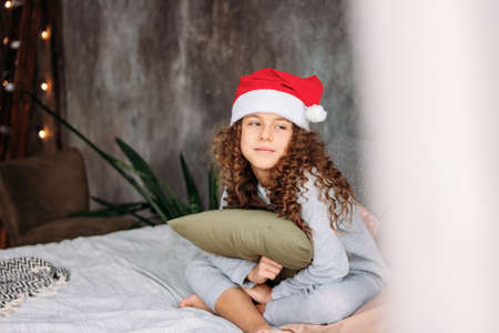 Curly haired beautiful tween girl in Santa hat and pajamas sitting on the bed with pillow, christmas morning time