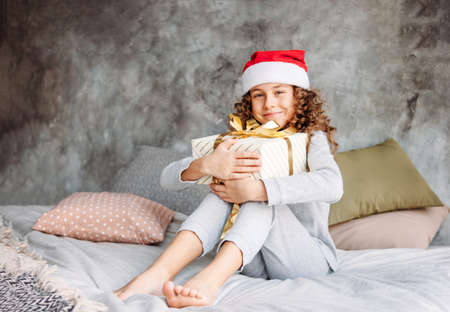 Curly haired beautiful tween girl in Santa hat and pajamas sitting on the bed with big gift box, christmas morning time