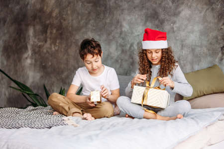 Cute tween children in Santa hats and pajamas open christmas gift boxes on the bed with pillow, christmas morning time, kids party