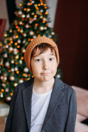Attractive funny tween boy with dark hair in hat looking at the camera on christmas tree background Zdjęcie Seryjne