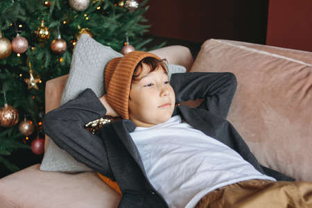 Attractive funny tween boy with dark hair in hat waiting new year on sofa on the christmas tree background