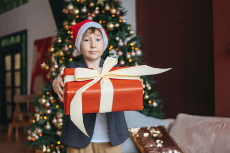 Attractive funny tween boy with dark hair in santa hat gives present at camera on the christmas tree background