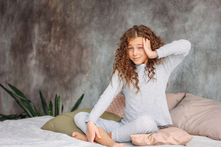 Curly haired beautiful tween girl in pajamas just waking up and sitting on the bed with pillow, morning time