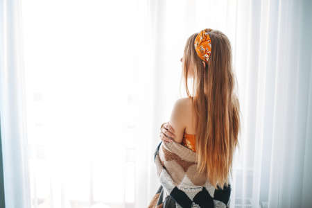 Beautiful smiling young woman fair long hair girl wearing in cozy knitted cardigan near window at the home