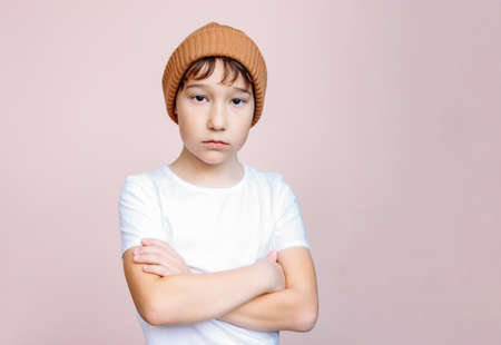 Attractive tween unhappy boy with dark hair in hat looks at camera isolated on the light pink background Zdjęcie Seryjne