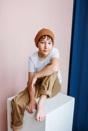 Fashionable attractive tween boy with dark hair in hat sitting on the white cube in studio, kids modeling Zdjęcie Seryjne