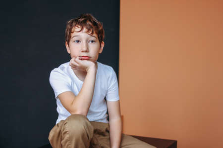 Attractive thinking tween boy with dark hair sitting on the black and beige background Zdjęcie Seryjne