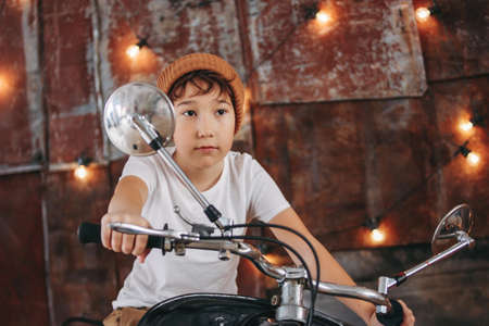 Funny cute tween boy in hat and white t-shirt on the motorcycle presents himself as adult man and cool