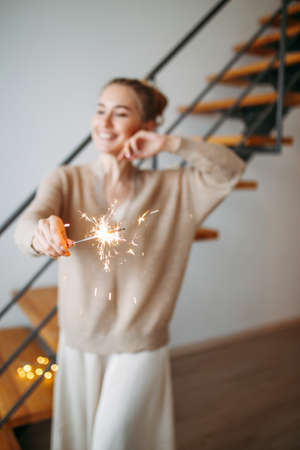 Young beautiful happy girl with blonde hair in silk dress and cozy beige cardigan holds the sparklers at the home, selective focus