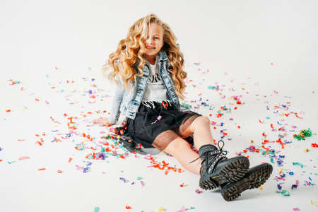 Happy fashionably dressed curly hair tween girl in in a denim jacket and black tutu skirt and rough boots sitting on the white background with colorful confetti. Zdjęcie Seryjne
