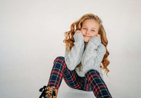 Beauty fashion portrait of smiling curly hair tween girl in cozy knitted sweater and plaid pants on he white background isolated