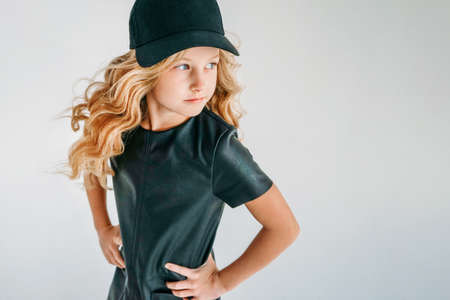 Beauty fashion portrait of smiling curly hair tween girl in black leather dress and baseball cap on the white background isolated Zdjęcie Seryjne