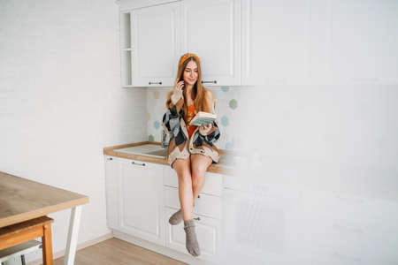 Beautiful smiling young woman fair long hair girl wearing in cozy knitted cardigan reading book sitting on kitchen work surface at the home Zdjęcie Seryjne