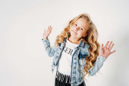 Smiling curly hair tween girl in denim jacket and black tutu skirt on white background isolated Zdjęcie Seryjne
