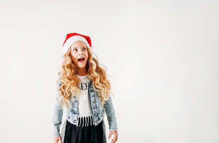 Surprised curly hair tween girl in santa hat and denim jacket and black tutu skirt on the white background isolated Zdjęcie Seryjne