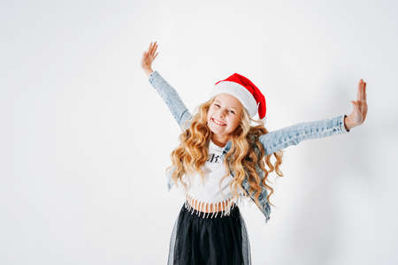 Happy fashionably dressed curly hair tween girl in santa hat, denim jacket and black tutu skirt on the white background Zdjęcie Seryjne