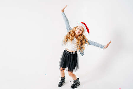 Happy fashionably dressed curly hair tween girl in santa hat, denim jacket and black tutu skirt on white background Zdjęcie Seryjne