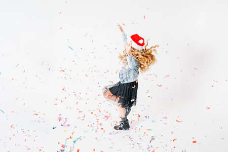 Happy fashionably dressed curly hair tween girl in santa hat, denim jacket and black tutu skirt on the white background with colorful confetti