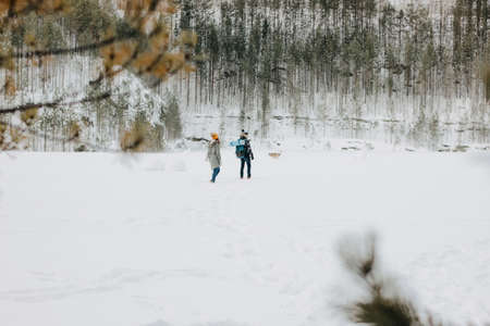 The young couple with dog haski at the forest nature park in winter. Travel adventure concept