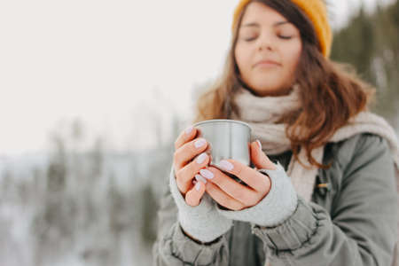 Brunette girl in yellow knitted hat with metal mug of hot tea in the forest outdoors in winter