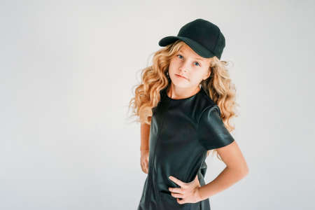 Beauty fashion portrait of smiling curly hair tween girl in black leather dress and baseball cap on the white background