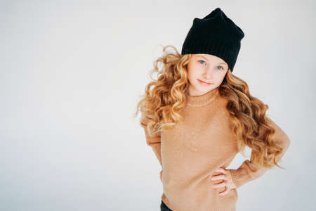 Beauty fashion portrait of smiling curly hair tween girl in black hat and beige sweater on the white background isolated