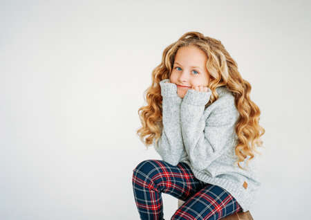 Beauty fashion portrait of smiling curly hair tween girl in cozy knitted sweater and plaid pants on white background Zdjęcie Seryjne