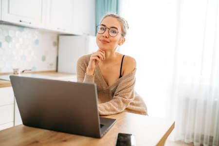 Beautiful smiling young woman fair long hair girl in glasses wearing in cozy knitted sweater using laptop at the bright kitchen Zdjęcie Seryjne