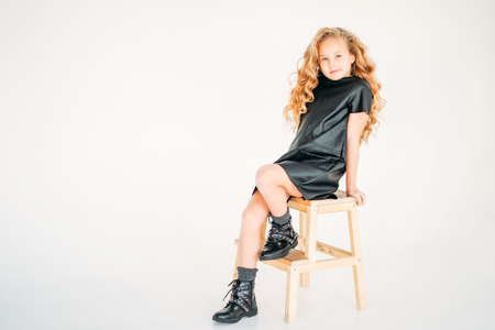 Beauty fashion portrait of smiling curly hair tween girl in black leather dress on the white background