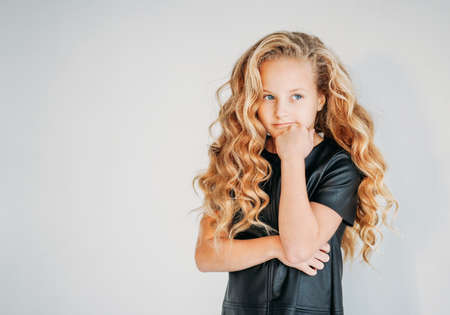 Thinking curly hair tween girl in black leather dress on the white background Zdjęcie Seryjne