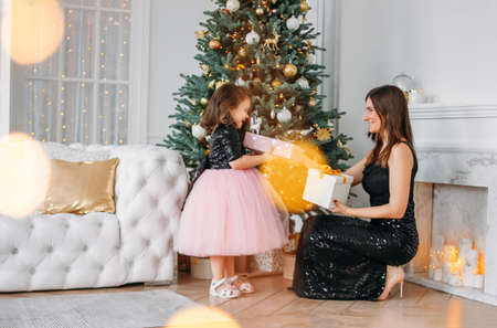 Young mother and daughter in evening dresses give each other gifts on background of the Christmas tree
