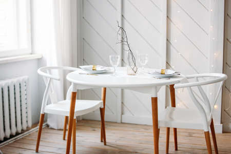 Festive table set for two, minimalistic Christmas decor. Scandinavian interior