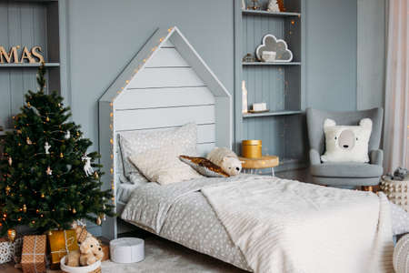 The wooden children bed with pillows and toys. Minimalistic Christmas decor. Scandinavian interior Zdjęcie Seryjne