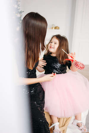 Young mother and daughter with red candy in the evening dresses on background of Christmas tree Stock Photo