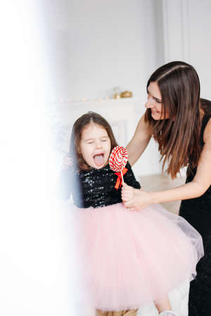 Young mother and daughter with red candy in evening dresses on background of Christmas tree Stock Photo