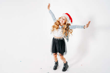 Happy fashionably dressed curly hair tween girl in santa hat, denim jacket and black tutu skirt on white background with colorful confetti