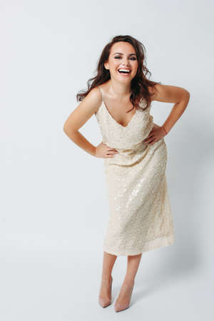 Happy beautiful brunette young woman dressed in light evening dress with sequins on the white background isolated