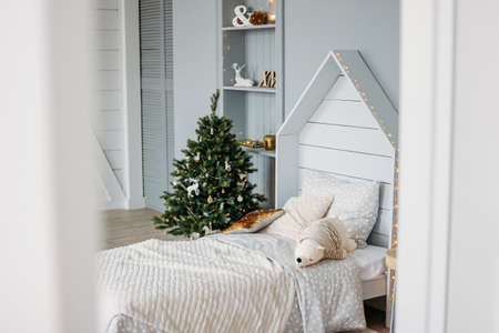The wooden children bed with pillows and toys. Minimalistic Christmas decor