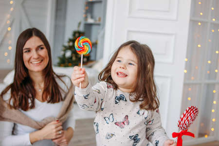 Young mother and daughter with  candies in on background of the Christmas tree Stock Photo