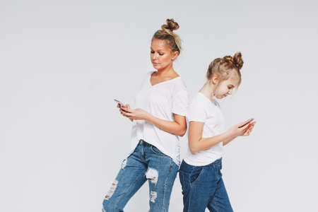 Blonde mom and daughter in the white t-shirts and jeans using mobile phones gadgets concept isolated on white background