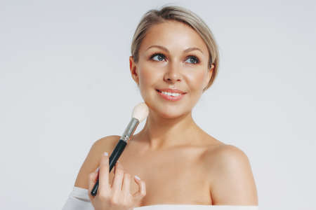 Beauty portrait of blonde smiling woman 35 year plus holding blush brush near clean fresh face isolated on the white background