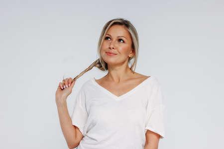 Charmante blonde lächelnde Frau 35 Jahre plus sauberes, frisches Hautgesicht mit dem Halten der Haare und dem Nachschlagen isoliert auf dem weißen Hintergrund