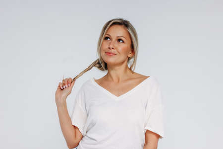 Charming blonde smiling woman 35 year plus clean fresh skin face with holding hair and looking up isolated on the white background