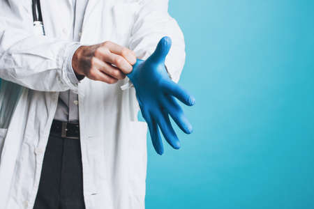 Crop photo of man doctor in white coat puts on rubber medical gloves  isolated on the blue background